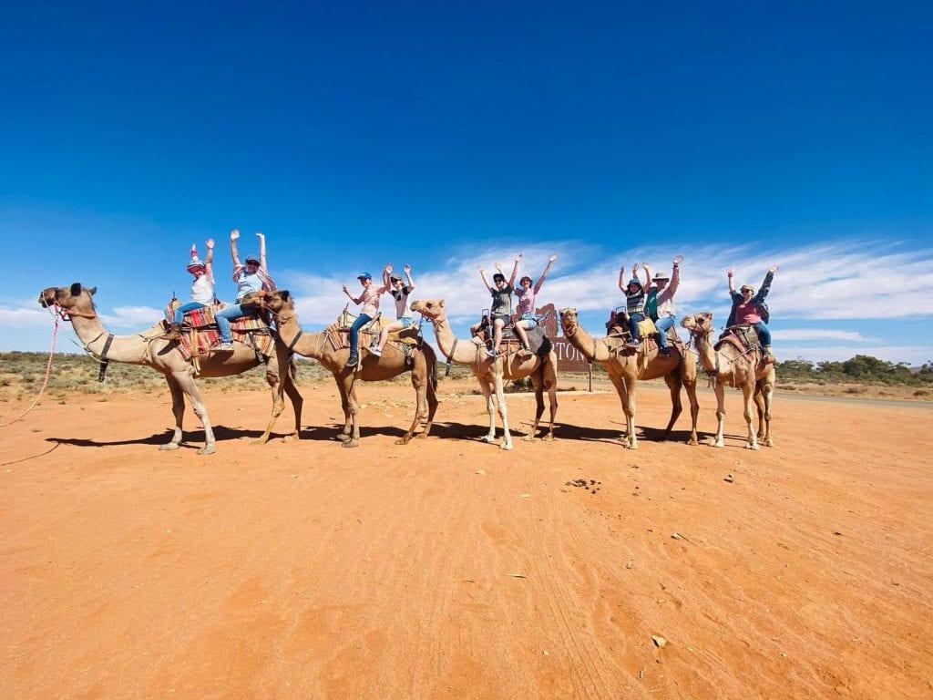 Happy people enjoying a camel ride in Silverton